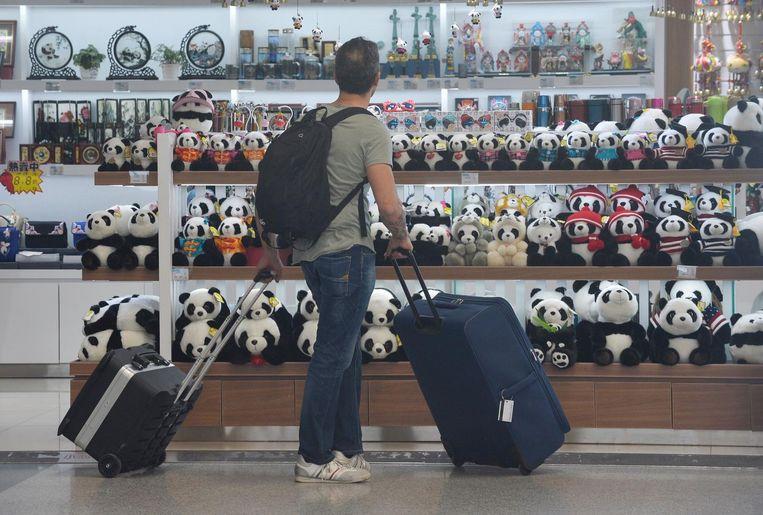 Een toerist bekijkt de panda souvernirshop het vliegveld van Chengdu. Beeld anp