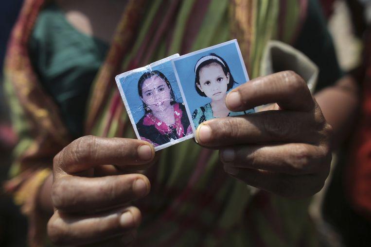 Een vrouw toont foto's van haar dochter die is omgekomen bij de ramp met het Rana Plaza-complex in Bangladesh en haar kleindochter. Beeld Reuters