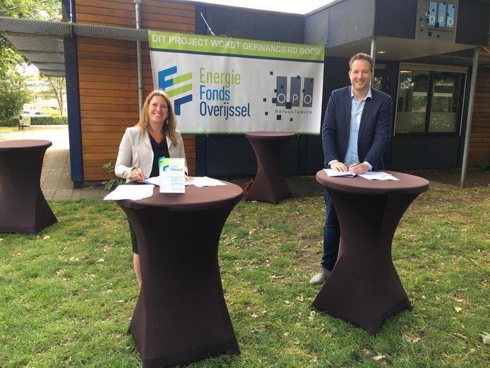 Algemeen directeur Anouk Blüm van het Energiefonds Overijssel en directeur-bestuurder Jasper Kok van de Stichting Openbaar Primair Onderwijs Hof van Twente ondertekenen de overeenkomst.