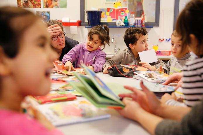 Leerlingen van een basisschool in een AZC leren lezen door middel van kinderboeken.
