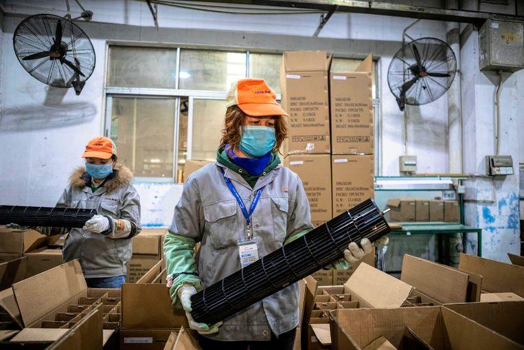 Werknemers dragen beschermende maskers in de Sunwill fabriek die plastic onderdelen produceert.Foshan, China. Beeld EPA
