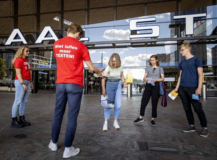 Folders en mondkapjes worden uitgedeeld bij de aftrap van de campagne voor Rotterdamse studenten, om hen te wijzen op de corona-maatregelen en het testen bij klachten.