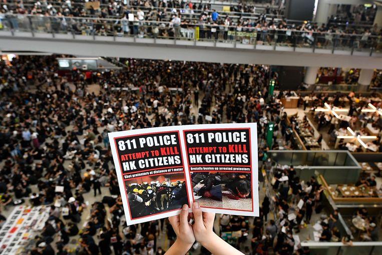 """Gisteren werden alle vluchten afgelast omdat duizenden de luchthaven bezetten. Ze hadden affiches bij, met foto's die tonen """"hoe een politiemacht het volk van Hongkong probeert te vermoorden""""."""