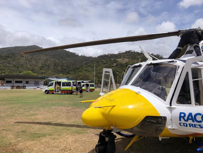 Sur cette photo fournie par RACQ CQ Rescue, un hélicoptère et des ambulances utilisés pour le sauvetage de deux touristes attaqués par un requin sont stationnés sur un terrain de sport, près de Airlie Beach, Australie.