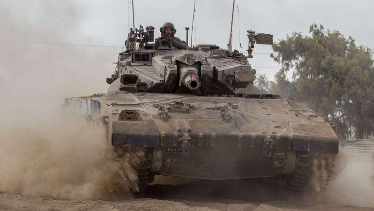 Een tank van het Israëlische leger rijdt langs de grens tussen Israël en de Gazastrook. Beeld afp