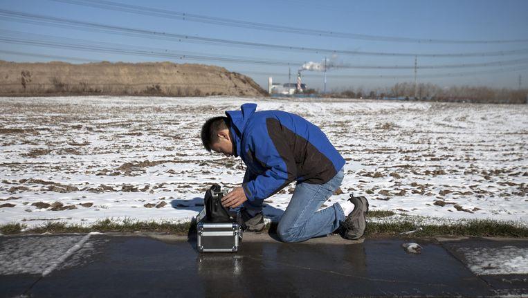 Een vrijwilliger van Green Beagle meet de luchtkwaliteit vlakbij een afvalverbrandingsinstallatie in Peking. Beeld ap