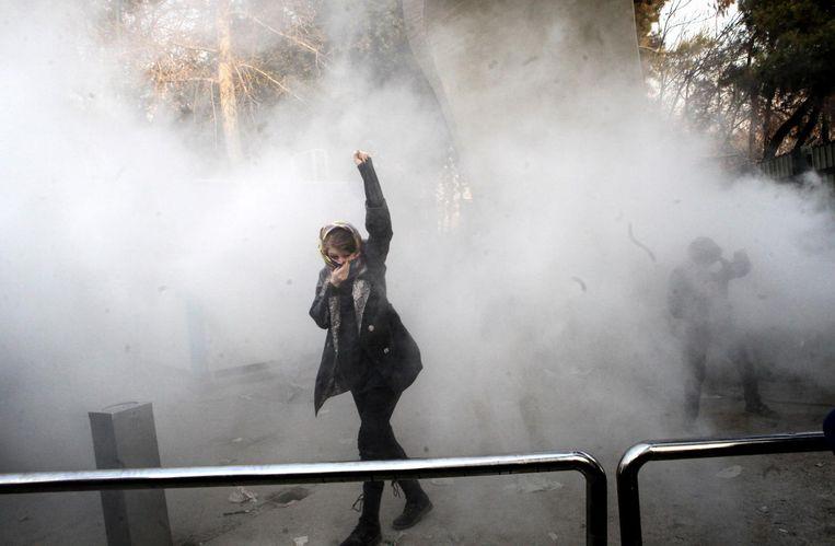 Een Iraanse studente protesteert in Teheran. Sinds vorige week donderdag zijn in Iran al zeker 21 doden gevallen bij de demonstraties. Beeld epa