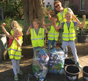 Een groepje Wijkhelden toont trots de twee zakken zwerfvuil die ze in drie kwartier in hun wijk hebben verzameld.