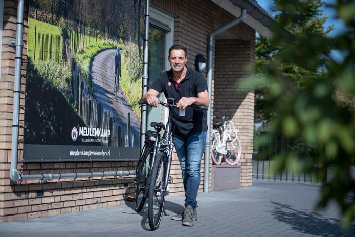 Fietsenhandelaar Martin Meulenkamp met en op een elektrische fiets was een van de gedupeerden van oplichtster Truus W. uit Almelo.