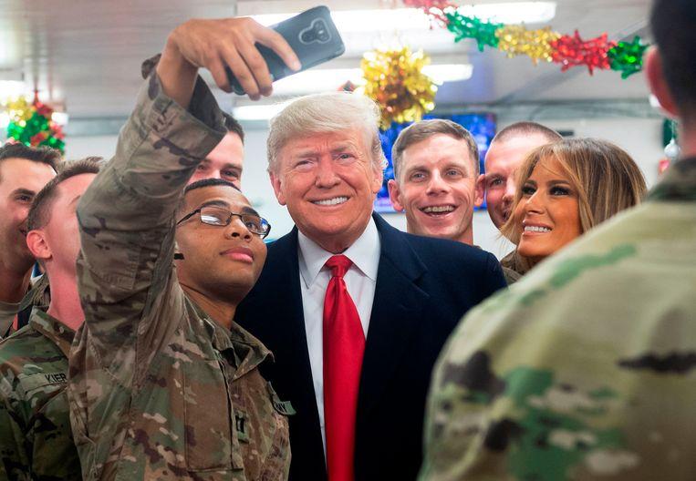 President Trump en first lady Melania poseren op de luchtmachtbasis Al Asad in Irak voor een selfie met Amerikaanse militairen.  Beeld AFP