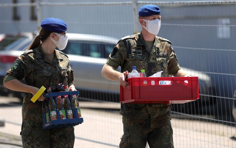Duitse militairen van een gezamenlijke mobiele medische testpost van het Rode Kruis en de Bundeswehr, maken zich op om Covid-19 tests af te nemen en te analyseren van mensen die in quarantaine zitten in de plaats Verl in Noord-Rijnland-Westfalen. Beeld EPA