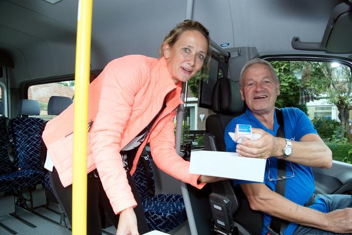 Buurtbusvoorzitter Bertine Grootemarsink deelt uit, chauffeur Bennie Bosch ontvangt. De aansluiting van Lemele op de Buurtbus Vilsteren werd maandagochtend gevierd.
