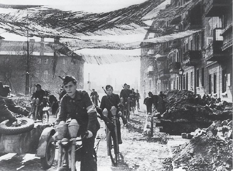 Jongens fietsen met pantservuisten aan het stuur naar het front in februari 1945. Foto uit besproken boek Beeld