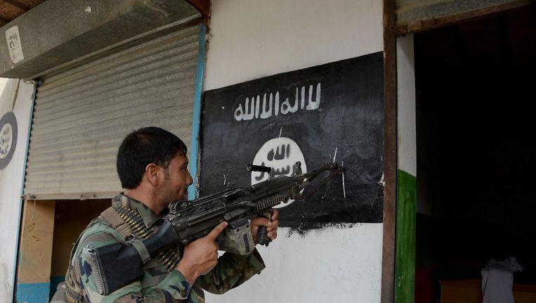 Een Afghaanse soldaat valt een huis binnen in Kot, vlakbij de Pakistaanse grens. Beeld afp