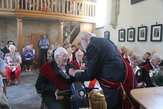 Koning Joop Peters van het Sint Jansgilde speldt bij Frans van de Rijdt de onderscheiding op.
