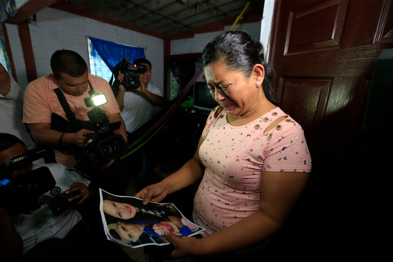 Grootmoeder Rosa Ramirez huilt, terwijl zij een foto van haar zoon en zijn gezin bekijkt.