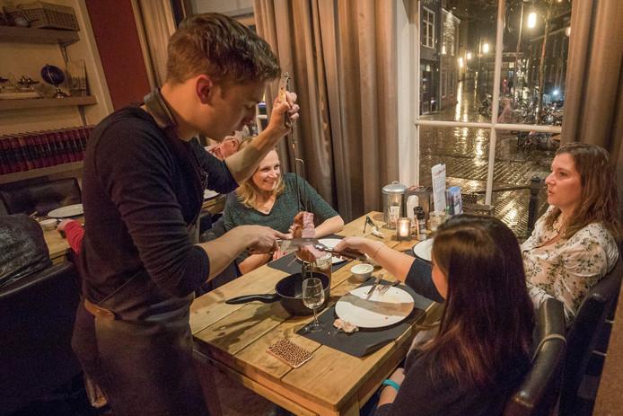 Gaucho Simeon Gouw snijdt het vlees aan tafel aan.
