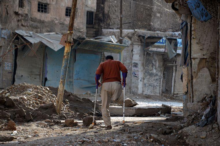 Op deze foto van gisteren wandelt een man die een been verloor met krukken door een verwoeste straat in Mosul.