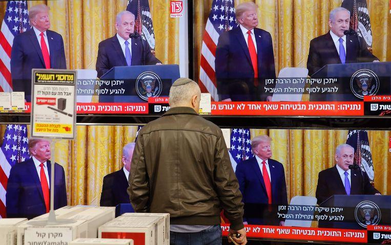 Een man bekijkt de persconferentie in Israël.