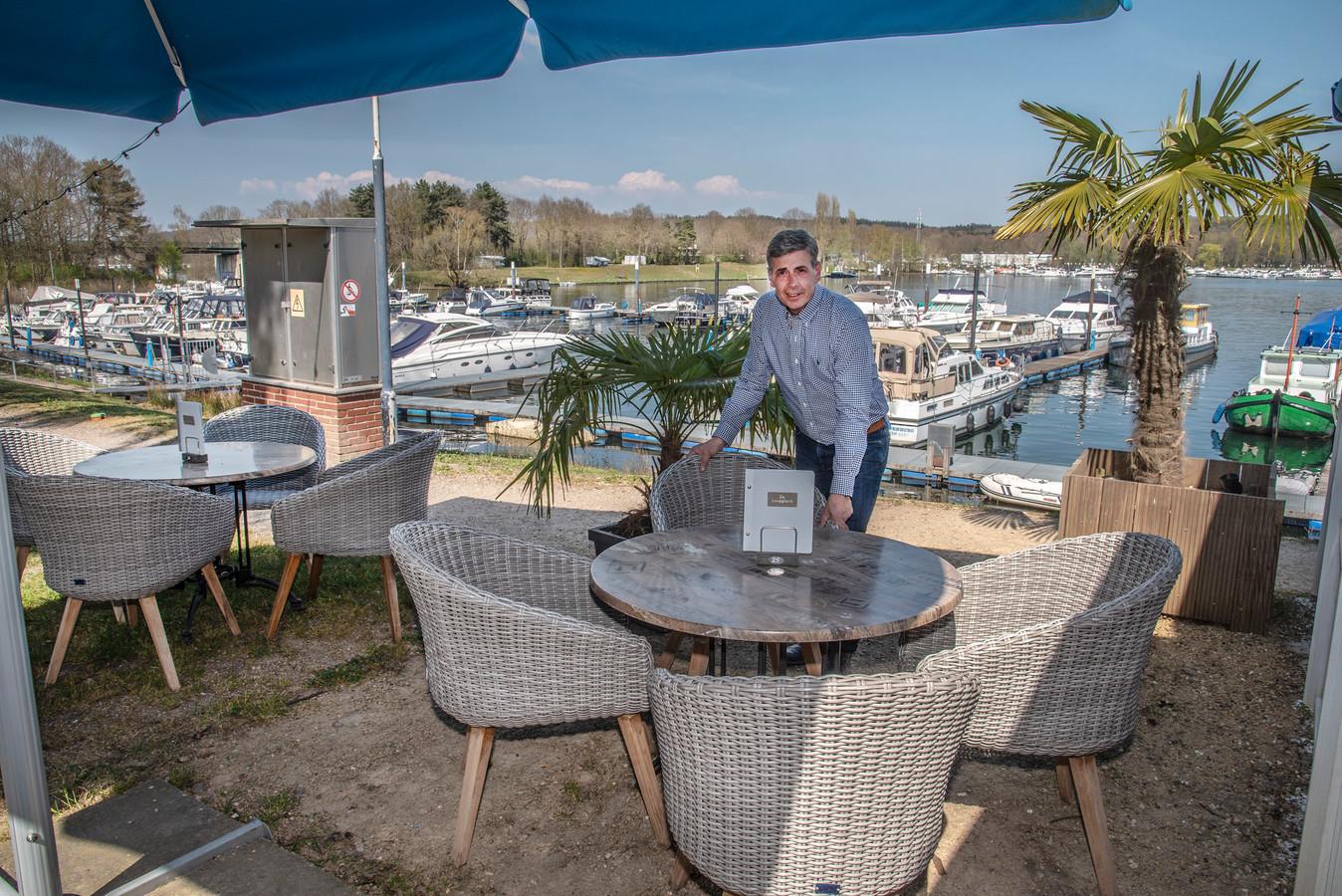 Hans Verhagen van restaurant De Loopplank in Middelaar is zijn terras aan het opknappen en zet alles meteen zover uit elkaat dat de gasten straks rustig kunnen zitten. Alles  anderhalve meter uit elkaar.