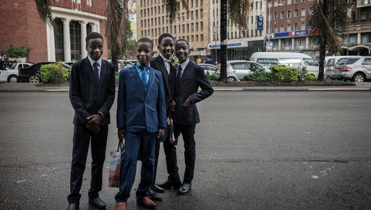 Vier jongens in Harare zijn op weg naar een bruiloft. Zimbabwe kent een relatief goed opgeleide bevolking, dankzij Mugabe. Beeld Chris de Bode