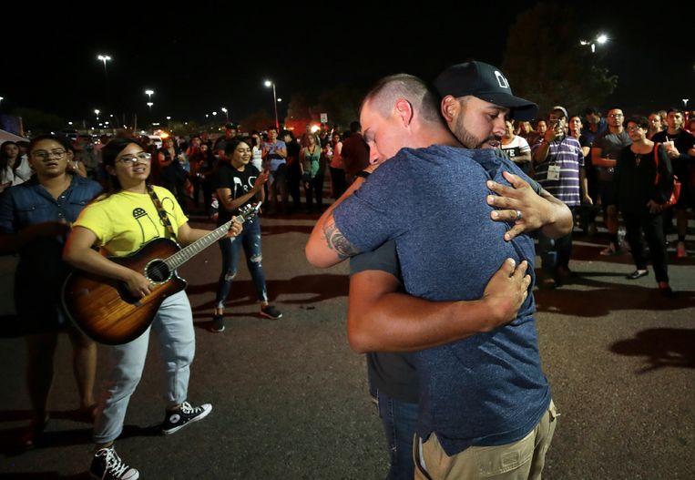 Bezoekers omhelzen elkaar op de gedenkplek in El Paso waar Patrick Crusius 22 mensen doodschoot. Beeld null
