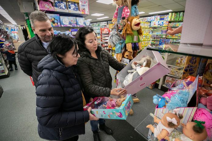 David Smits (links) en Jolanda Weijers (rechts) kijken in De Gestelse Bazar tussen de poppen. Op de voorgrond Jolanda's zus Margaret.