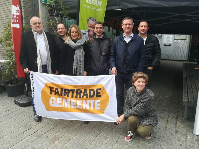 De mensen van de Noord-Zuidraad met bevoegd schepen Kurt Himpe en het Fairtrade-gemeente logo.