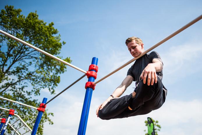 Glenn van Osch uit Hees deed in Dieren mee aan een demonstratiewedstrijd en hangt met zijn kin 'helemaal zen' aan de rekstok.