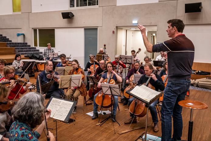 Dirigent Quentin Clare en Symfonie Orkest Eindhoven tijdens een repetitie voor het jubileumconcert.