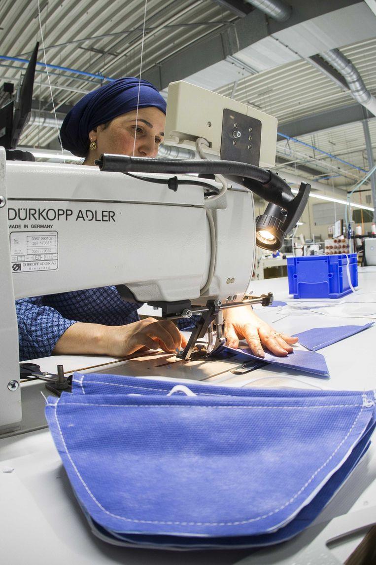 Medewerkers bereiden mondkapjes voor in een naaiatelier van beddenfabrikant Auping. Met DSM en Afpro produceert Auping sinds april mondkapjes. DSM en VDL gaan vanaf oktober mondkapjes maken in Helmond.  Beeld ANP
