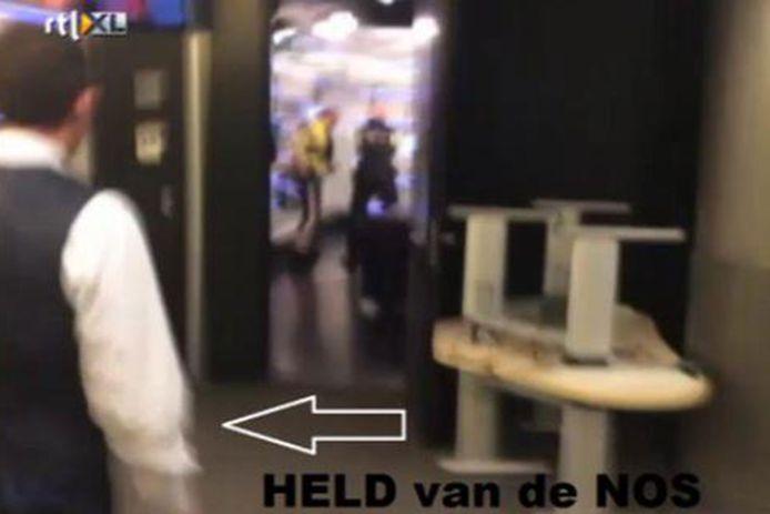 De portier loopt de studio uit nadat de politie de binnendringer heeft overmeesterd