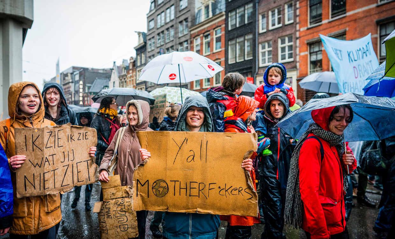 Deelnemers met borden en spandoeken tijdens de klimaatmars.  Beeld Freek Van Den Bergh