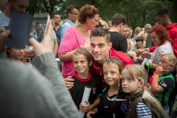 Keeper Joshua Smits poseert voor de foto met drie jonge fans.