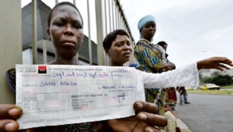 Een slachtoffer toont de vergoeding die ze van Trafigura kreeg. ( FOTO AFP) Beeld AFP