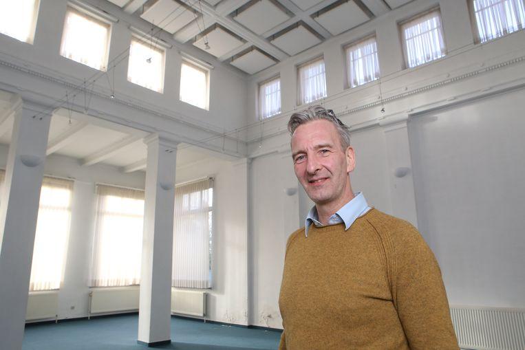 Tom Decuypere toont waar de vergaderzaal komt (hier waren vroeger de loketten van de Generale Bank gevestigd).