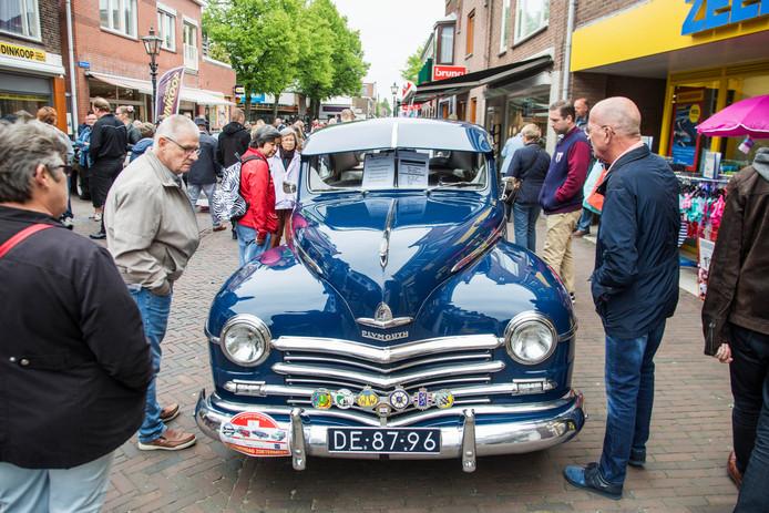 Bezoekers bewonderen op de Dorpsstraat een Plymouth Special de Luxe tijdens de Oldtimerdag in 2018.