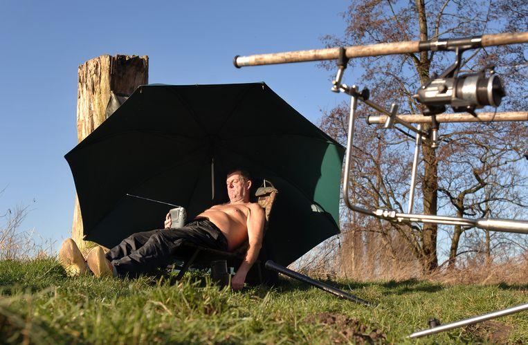 Een visser geniet van de warmte van de zon Beeld Marcel van den Bergh / de Volkskrant