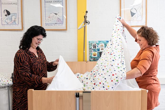 Claudine Hommel (links) doet voor aan de klas hoe je een instellingsbed opmaakt.