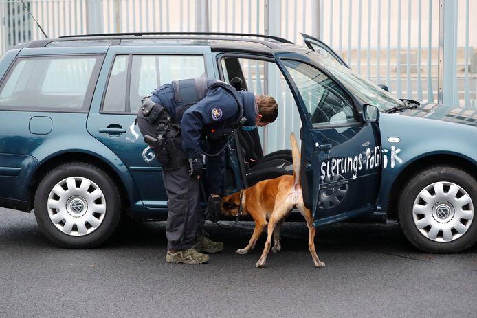 Een agent met hond onderzoekt de auto.