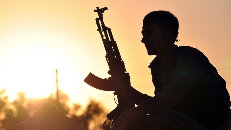 Een YPG-strijder bij zonsondergang. Beeld afp