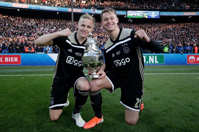 Donny van de Beek en Frenkie de Jong met de KNVB-beker die Ajax vorig seizoen won door Willem II in de finale met 4-0 te verslaan.