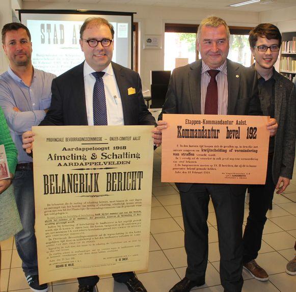 Burgemeester D'Haese en schepen Van Overmeire houden de affiche uit WOI vast.