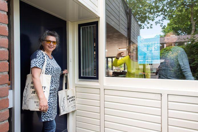 José Jonkers hangt een Ik vergeet je niet-tasje aan de voordeur van Gudy en Toine in de Haagse Beemden.