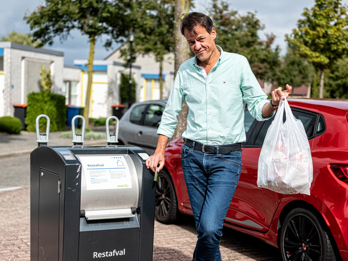 Tijs van den Brink bij een afvalcontainer.