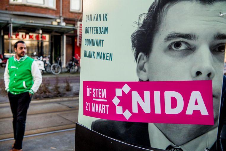 Medewerkers van de Rotterdamse politieke partij Nida bevestigen bij de Essalam moskee posters waarmee ze kiezers oproepen niet te stemmen op Leefbaar, Forum en PVV tijdens de gemeenteraadsverkiezingen. Beeld anp