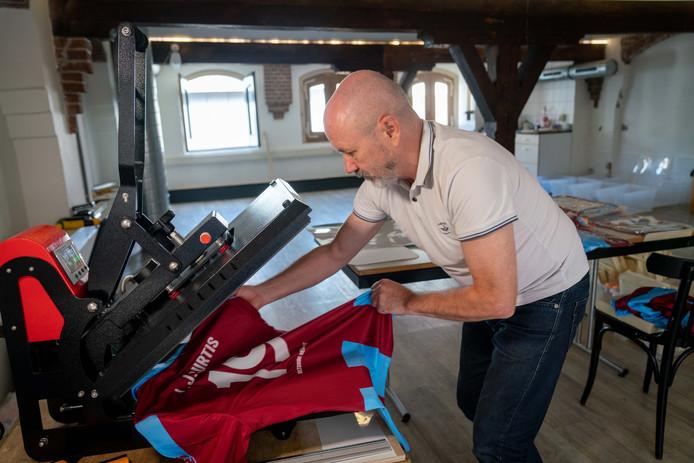 Gerry Delaney bedrukt een van zijn Battle Of Arnhem Remembrance-shirts in zijn studio aan de Korenmarkt.