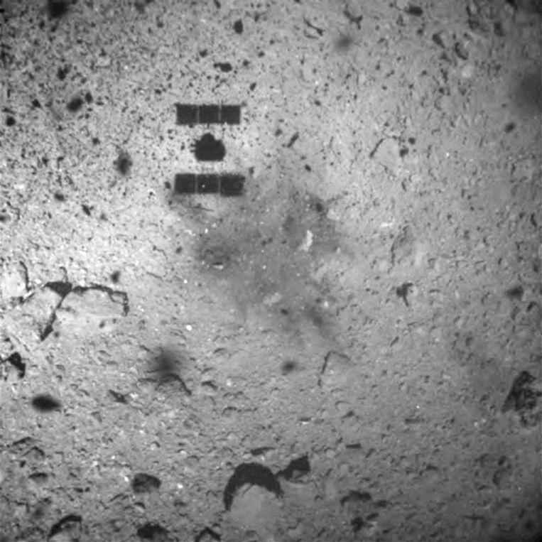 De schaduw van de Japanse ruimtesonde Hayabusa 2 is zichtbaar op asteroïde Ryugu, waarop de lander vrijdag neerstreek om materiaal te verzamelen en terug te brengen naar aarde.  Beeld EPA/JAXA/TOKYO UNIVERSITY