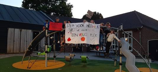 Leerlingen van basisschool De Regenboog in Wijbosch maken de aanwezigen van de dorpsvergadering duidelijk dat zij vóór een hek op hun schoolplein zijn.
