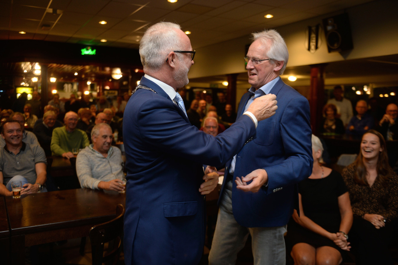 Burgemeester Gerard van den Hengel (links) speldt Harrie Besselink de koninklijke onderscheiding op.